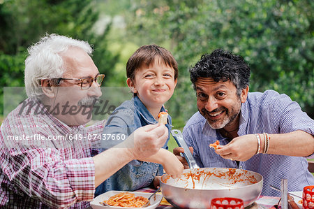 Boy enjoying a meal together with father and grandfather Stock Photo - Premium Royalty-Free, Image code: 649-07437660