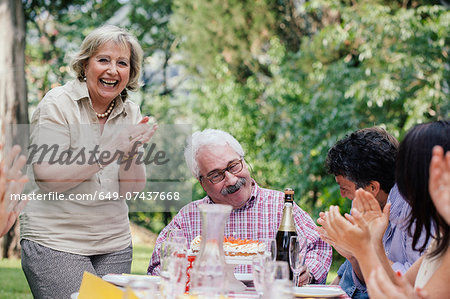 Senior man being presented with cake at birthday party Stock Photo - Premium Royalty-Free, Image code: 649-07437668
