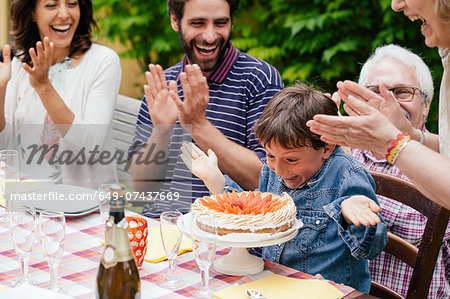 Boy being surprised with birthday cake Stock Photo - Premium Royalty-Free, Image code: 649-07437669