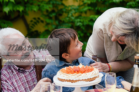 Grandparents surprising grandson with birthday cake Stock Photo - Premium Royalty-Free, Image code: 649-07437671