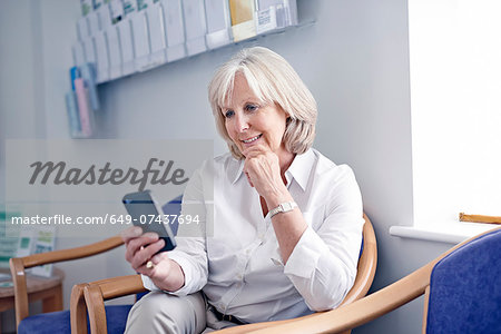 Mature female patient looking at mobile phone in hospital waiting room Stock Photo - Premium Royalty-Free, Image code: 649-07437694