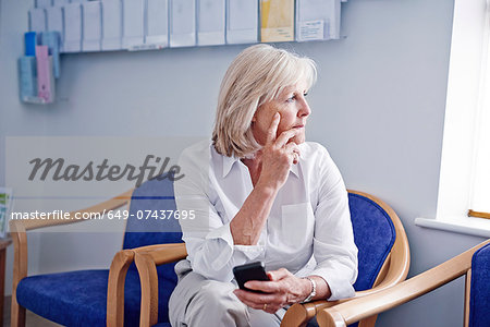 Mature female patient with mobile phone in hospital waiting room Stock Photo - Premium Royalty-Free, Image code: 649-07437695
