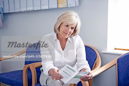 Mature female patient reading leaflet in hospital waiting room Stock Photo - Premium Royalty-Free, Image code: 649-07437696