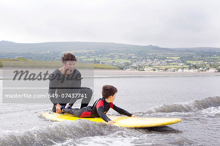 Father teaching son how to surf Stock Photo - Premium Royalty-Free, Image code: 649-07437741