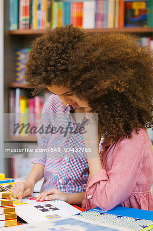 Brother and sister browsing design book in library Stock Photo - Premium Royalty-Free, Image code: 649-07437765
