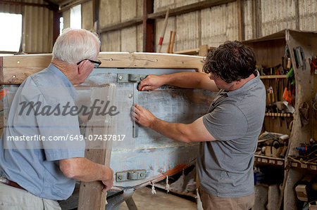 Father watching son restore boat in workshop Stock Photo - Premium Royalty-Free, Image code: 649-07437817
