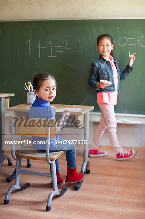 Girl by blackboard and sister at desk Stock Photo - Premium Royalty-Free, Image code: 649-07437855