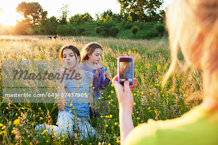 Mother taking photograph of girls blowing bubbles Stock Photo - Premium Royalty-Free, Image code: 649-07437905