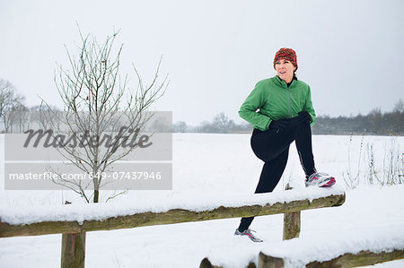 Female jogger stretching before run in snow covered scene Stock Photo - Premium Royalty-Free, Image code: 649-07437946