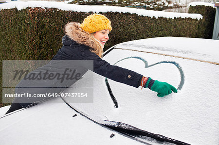 Woman drawing heart shape on snow covered windscreen Stock Photo - Premium Royalty-Free, Image code: 649-07437954