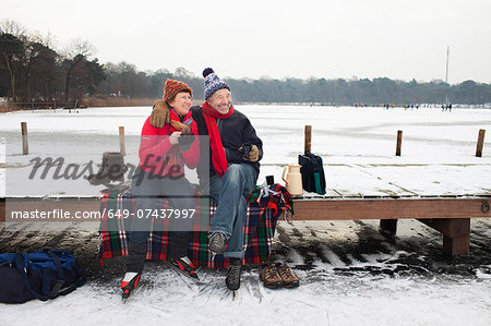 Couple sitting on pier having hot drink Stock Photo - Premium Royalty-Free, Image code: 649-07437997