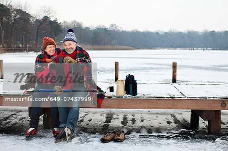 Couple sitting on pier having hot drink Stock Photo - Premium Royalty-Free, Image code: 649-07437999