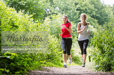 Women jogging through forest Stock Photo - Premium Royalty-Free, Image code: 649-07438051