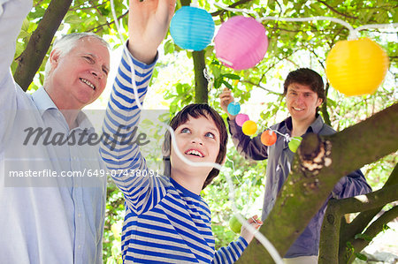 Three generation family putting fairy lights in tree Stock Photo - Premium Royalty-Free, Image code: 649-07438091