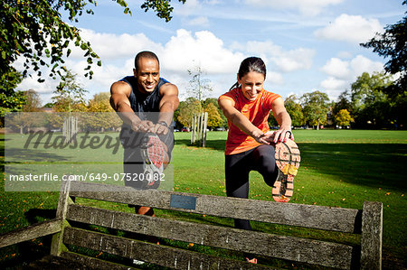 Couple stretching legs on park bench Stock Photo - Premium Royalty-Free, Image code: 649-07520082