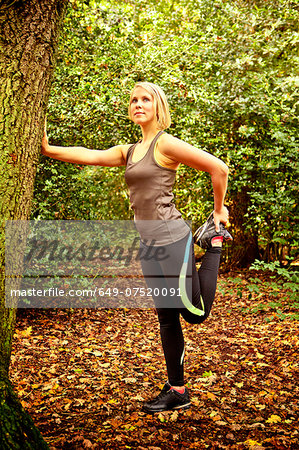 Woman stretching legs in woods Stock Photo - Premium Royalty-Free, Image code: 649-07520091