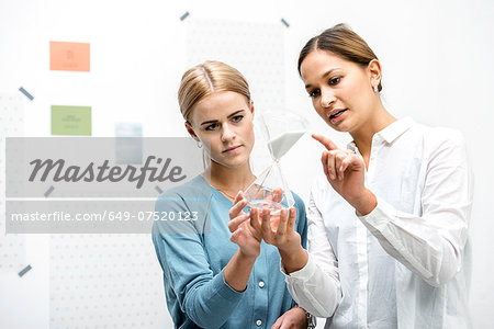Female colleagues discussing workings of the hourglass Stock Photo - Premium Royalty-Free, Image code: 649-07520123