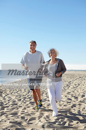 Couple jogging on beach Stock Photo - Premium Royalty-Free, Image code: 649-07520148