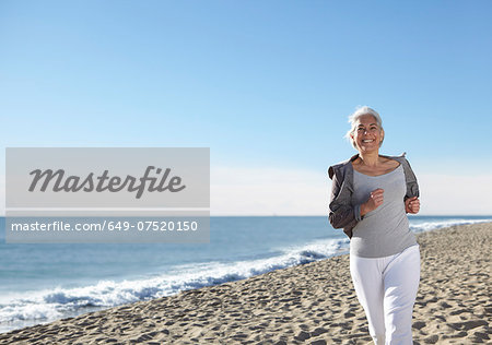 Mature woman jogging on beach Stock Photo - Premium Royalty-Free, Image code: 649-07520150
