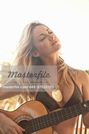 Woman in bikini playing guitar Stock Photo - Premium Royalty-Free, Image code: 649-07520191