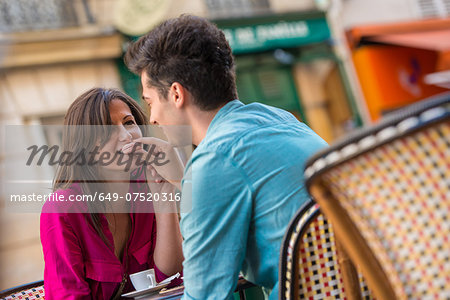 Young couple sharing macaroon at pavement cafe, Paris, France Stock Photo - Premium Royalty-Free, Image code: 649-07520316