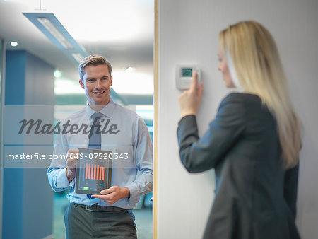 Office workers adjusting heating thermostat and recording information on digital tablet Stock Photo - Premium Royalty-Free, Image code: 649-07520343
