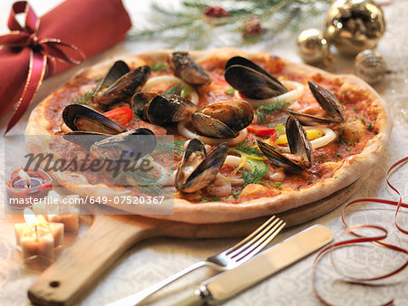 Homemade seafood pizza topped with calamari, prawns and mussels with festive decorations Stock Photo - Premium Royalty-Free, Image code: 649-07520367