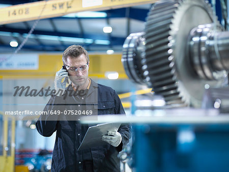 Engineer using mobile phone in engineering factory Stock Photo - Premium Royalty-Free, Image code: 649-07520469