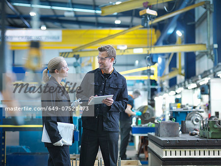 Workers in discussion in engineering factory Stock Photo - Premium Royalty-Free, Image code: 649-07520473