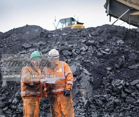 Workers in discussion in front of coal stocks in surface coal mine Stock Photo - Premium Royalty-Free, Image code: 649-07520511