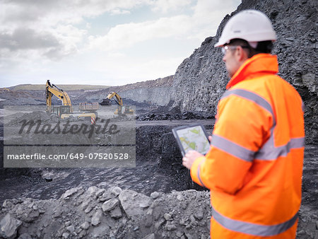 Miner checks plans on digital tablet in surface coal mine Stock Photo - Premium Royalty-Free, Image code: 649-07520528
