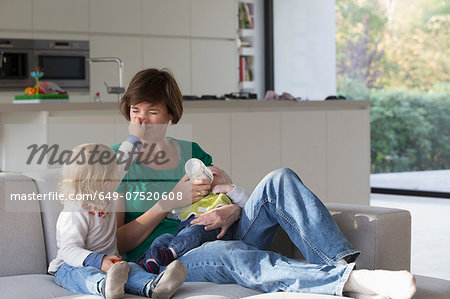 Mother, baby boy and female toddler sitting on sofa Stock Photo - Premium Royalty-Free, Image code: 649-07520608