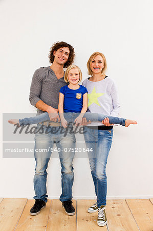 Studio portrait of couple holding up daughter Stock Photo - Premium Royalty-Free, Image code: 649-07520644