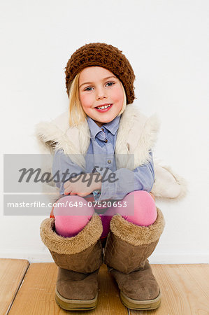 Studio portrait of young girl in oversize boots Stock Photo - Premium Royalty-Free, Image code: 649-07520653
