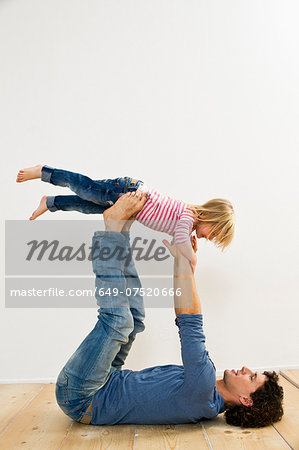 Studio shot of father lifting up daughter whilst lying on back Stock Photo - Premium Royalty-Free, Image code: 649-07520666