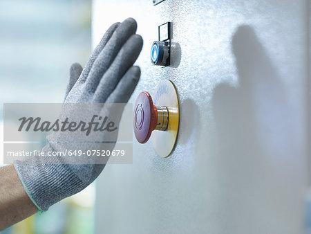 Engineer pressing emergency stop in engineering factory, close up Stock Photo - Premium Royalty-Free, Image code: 649-07520679