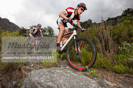 Young couple riding mountain bikes on dirt track Stock Photo - Premium Royalty-Free, Image code: 649-07520853