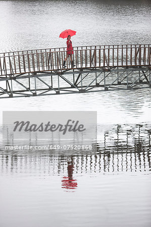 Young woman in red crossing footbridge in rain Stock Photo - Premium Royalty-Free, Image code: 649-07520860