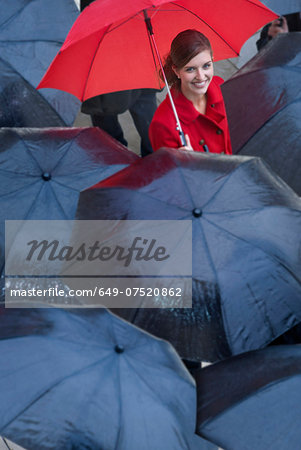 Young woman with red umbrella amongst black umbrella's Stock Photo - Premium Royalty-Free, Image code: 649-07520862