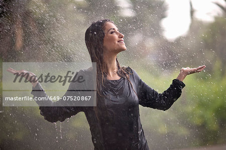 Drenched young woman with arms open in rainy park Stock Photo - Premium Royalty-Free, Image code: 649-07520867