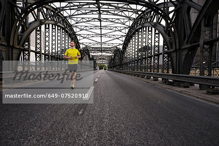Young male athlete running on bridge Stock Photo - Premium Royalty-Free, Image code: 649-07520910