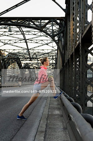 Young female runner stretching legs on bridge Stock Photo - Premium Royalty-Free, Image code: 649-07520922