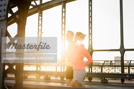 Young male and female running on bridge Stock Photo - Premium Royalty-Free, Image code: 649-07520925
