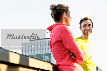 Young male and female runners talking on bridge Stock Photo - Premium Royalty-Free, Image code: 649-07520929