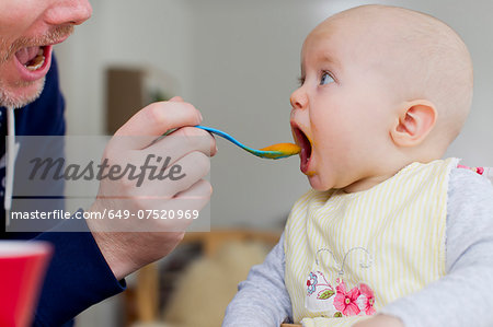 Father spoon feeding baby daughter Stock Photo - Premium Royalty-Free, Image code: 649-07520969