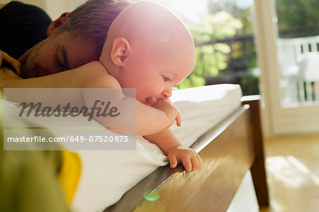 Father and baby daughter lying on bed Stock Photo - Premium Royalty-Free, Image code: 649-07520973