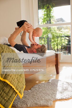 Father lifting baby daughter on bed Stock Photo - Premium Royalty-Free, Image code: 649-07520974