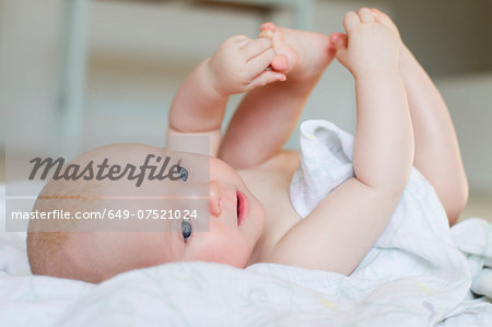 Baby girl lying on back Stock Photo - Premium Royalty-Free, Image code: 649-07521024