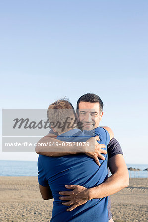 Mature male couple hugging on beach Stock Photo - Premium Royalty-Free, Image code: 649-07521039