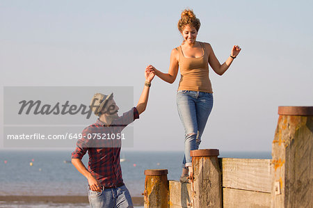 Young woman balancing on groynes holding man's hand Stock Photo - Premium Royalty-Free, Image code: 649-07521051